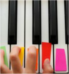 Amy Recchia Music Therapy Hudson Valley image of color-coded stickers on piano keys and a hand playing them.